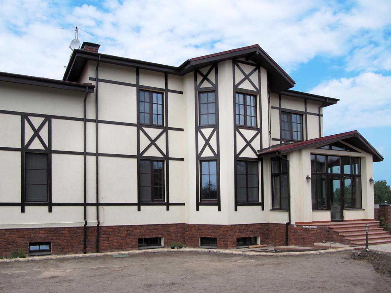 Коттедж с деревянными окнами и входной группой из массива дерева сбоку