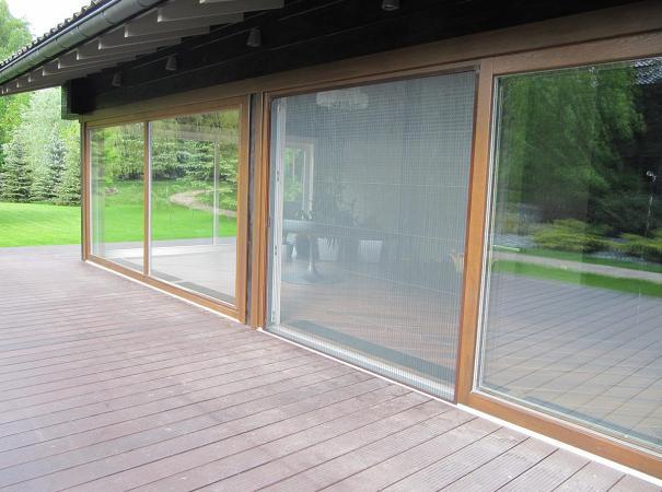 Остекление входной группы панорамными окнами из дерева, патио с установленной сектой плиссе