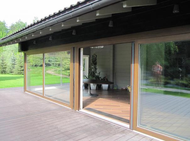Остекление входной группы панорамными окнами из дерева, патио с установленной сектой плиссе в открытом состоянии